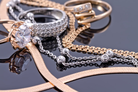 Photo pour Gold, silver rings and chains of different styles are lying together on the reflecting surface - image libre de droit