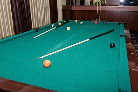 Worn pool table with a cue and balls in the great hall of the guests in the restaurant