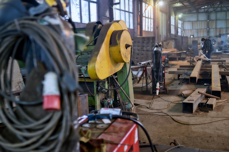 Foto de Working atmosphere in an old welding shop with a focus on old hydraulic guillotine and metal profiles - Imagen libre de derechos