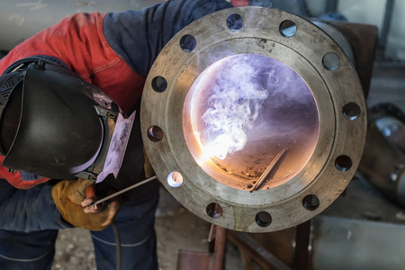 Photo pour Welding works on production of the pipeline unit-welding of the pipe and thick-walled flange - image libre de droit