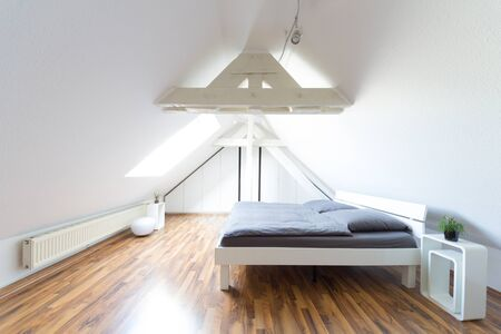 Foto de Wide angle view of modern, bright, puristic attic bedroom with double bed and gray bedclothes - Imagen libre de derechos