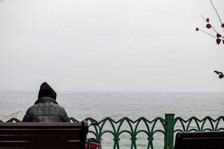 Foto de Lonely homeless woman in a hood on her head freezes on a bench near the sea alone - Imagen libre de derechos