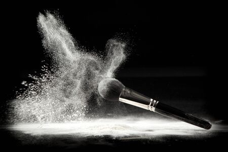 an image of a cosmetic powder brush, thrown in white loose powder, shot on black backgrownd.