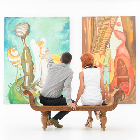 Photo for young caucasian couple sitting on a wooden bench in an art gallery pointing at some painting - Royalty Free Image