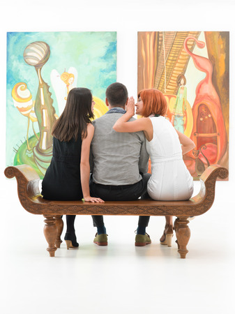 Photo for young people sitting on bench in front of two large paintings gossiping - Royalty Free Image