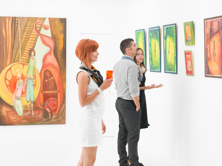 Photo for young caucasian people in an art gallery looking at paintings and talking about them - Royalty Free Image