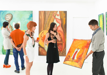 Photo for man holding and showing a colorful painting to other people in an art gallery - Royalty Free Image