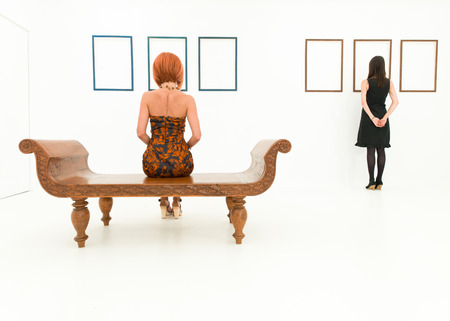 Photo for rear view of two women in a white room looking at empty frames displayed on walls in front of them - Royalty Free Image