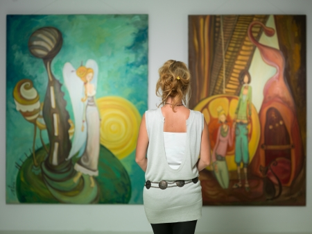 Photo for rear view of younga caucasian woman stading in an art gallery in front of two large colorful paintings - Royalty Free Image