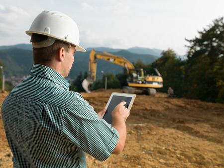 Photo pour back view of caucasian engineer standing on construction site checking plan on digital tablet - image libre de droit