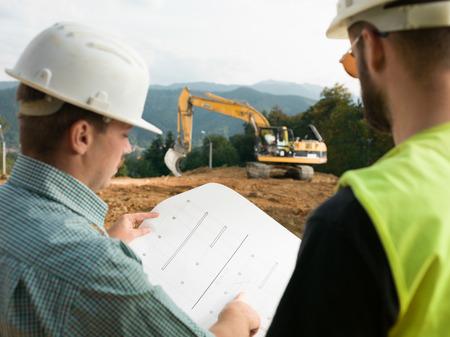 Foto de back view of two contractors looking at construction plan on worksite - Imagen libre de derechos