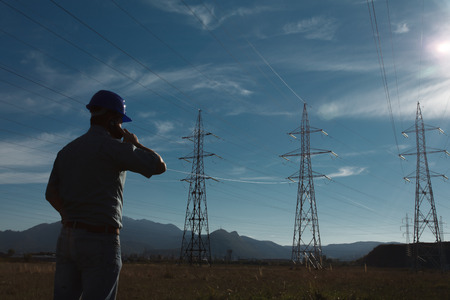 Photo pour silhouette of engineer standing on field with electricity towers, talking on the phone - image libre de droit
