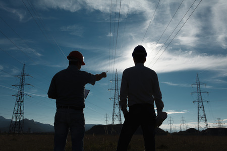 Photo pour silhouette of two engineers standing at electricity station at sundown - image libre de droit