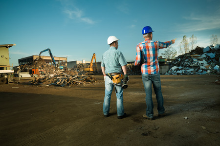 Foto de two caucasian engineers standing in recycling center outdoors, pointing at pile of scrap metal - Imagen libre de derechos