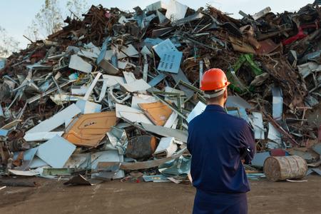 Foto de worker standing in front of pile of disposed objects in recycling center - Imagen libre de derechos