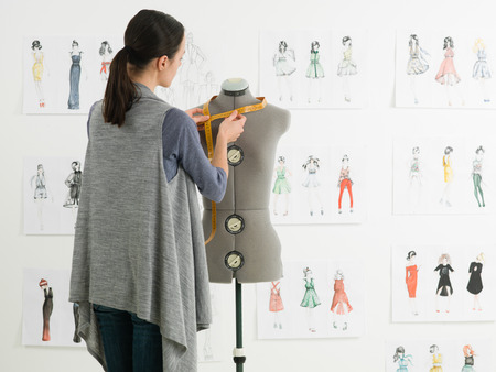 Photo pour young caucasian female fashion designer taking measurements on mannequin in her studio - image libre de droit