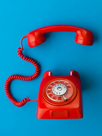 Photo pour red vintage phone with handset off the hook, on blue background - image libre de droit