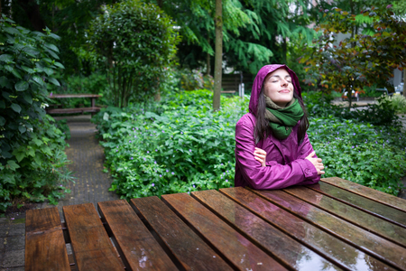 Foto de Beautiful young woman enjoying the rain in a garden decorated with eyes closed sits wooden table - Imagen libre de derechos