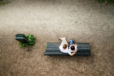 Photo for Caucasian young couple sitting on a park bench man protecting his girlfriend with love - Royalty Free Image