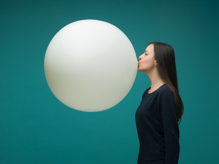 Photo pour funny young woman with long dark hair inflating huge balloon on blue background - image libre de droit