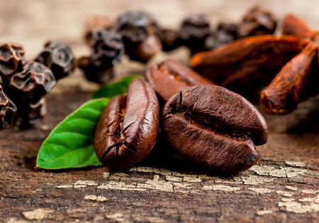 Foto de Coffee grains and green leaf on grunge wooden background - Imagen libre de derechos