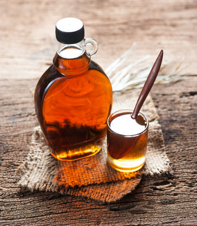 Photo for maple syrup in glass bottle on wooden table - Royalty Free Image