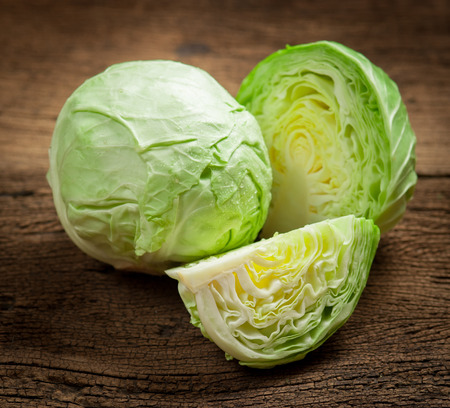 Foto de cabbage and cutted cabbage on wooden - Imagen libre de derechos