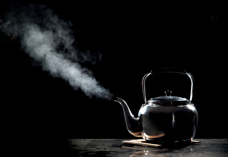 Photo for Tea kettle with boiling water on a black background - Royalty Free Image