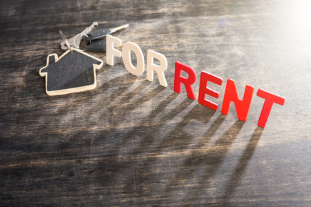 Photo pour Symbol of the house with text FOR RENT and key on wooden background - image libre de droit
