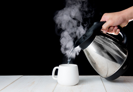 Foto de kettle pouring boiling water into a cup with smoke on wood table - Imagen libre de derechos