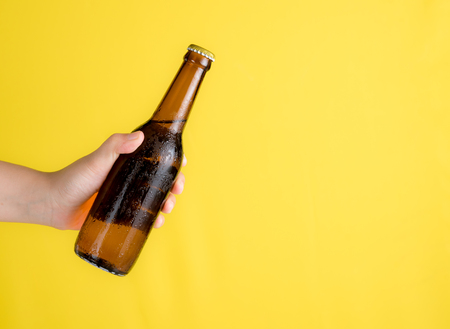 Photo pour Hand holding beer bottle with text space against yellow background - image libre de droit