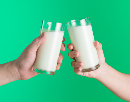 Foto de Two hands holding glass of milk on green background,Clinking glasses of milk - Imagen libre de derechos