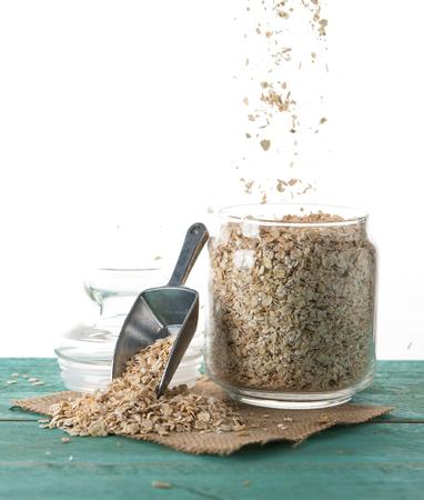 Foto de Oatmeal or oat flakes in jar on wood table against white background - Imagen libre de derechos