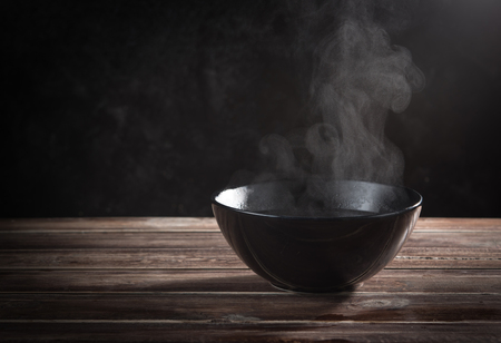 Photo pour Steam of hot soup with smoke in ceramic bowl against black cement wall - image libre de droit