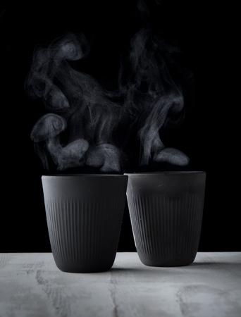 Cup of coffee with steam on wood over dark background