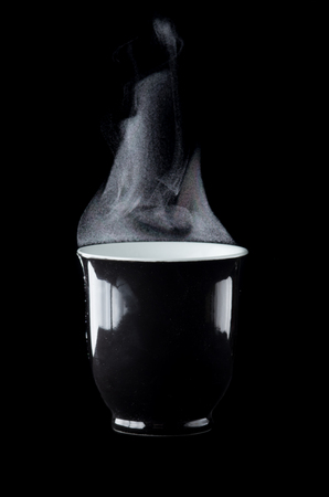 Cup of coffee with steam over dark background