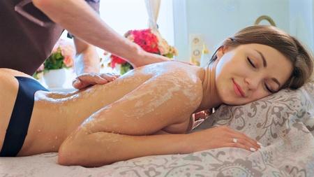 Photo pour Portrait of young pretty woman having scrubbing massage in beauty spa salon. - image libre de droit