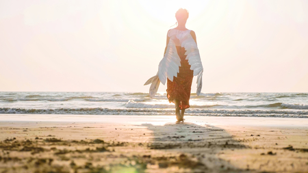 Photo for Beautiful female angel walking barefoot toward the sea at sunset. - Royalty Free Image