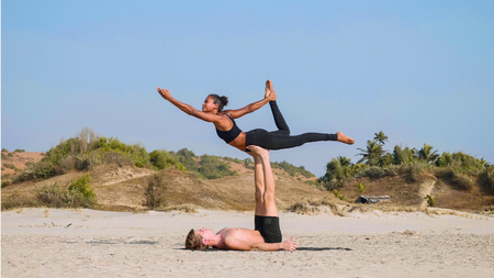 Foto de Fit sporty couple practicing acro yoga with partner together on the sandy beach. - Imagen libre de derechos