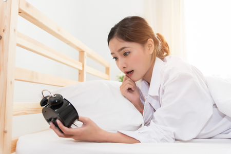 Photo pour Asian woman shocked when wake up by alarm clock because too late for meeting appointment or working. Lazy day and Hurry up concept. - image libre de droit