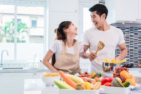 Photo pour Asian lovers or couples cooking so funny together in kitchen with full of ingredient on table. Honeymoon and Happiness concept. Valentines day and Sweet home - image libre de droit