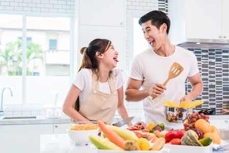 Photo for Asian lovers or couples cooking so funny together in kitchen with full of ingredient on table. Honeymoon and Happiness concept. Valentines day and Sweet home - Royalty Free Image