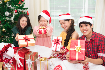 Photo for Group of young Asian people holding and giving gift box to you with Xmas tree background. Holiday and Festival concept. Christmas and New year event theme. Happy people wearing Santa hat. - Royalty Free Image