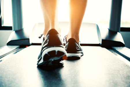 Foto de Close up of people who exercising on treadmill. Close-up of woman legs walking by treadmill in sports club. Fitness and Body build up concept. Workout and Strength training concept. Sport club theme. - Imagen libre de derechos