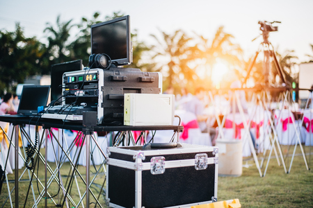 Foto de Dj mixing equalizer at outdoor in music party festival with party dinner table. Entertainment and Event organizer concept. Concert and Musical theme - Imagen libre de derechos
