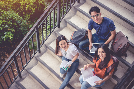 Foto de Three Asian young campus students enjoy tutoring and reading books together at stair. Friendship and Education concept. Campus school and university theme. Happiness and funny of learning in college. - Imagen libre de derechos