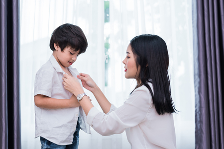 Foto de Young Asian mom dressed up son outfits for preparing go to school. Mother and son concept. Happy family and Home sweet home theme. Preschool and Back to school theme. - Imagen libre de derechos