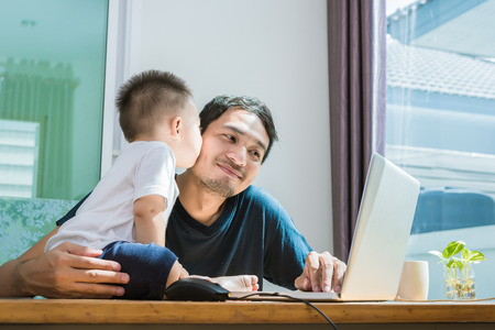 Photo pour Son kissing his father while using internet. People and Lifestyles concept. Technology and Happy family theme. Single dad theme. - image libre de droit