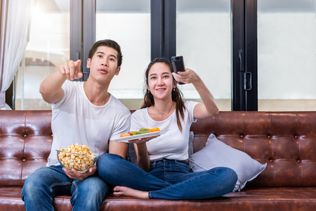 Photo pour Asisn couples watching television together on sofa in their home. People and lifestyles concept. Vacation and holiday concept. Honeymoon and pre-wedding theme. Happy family activity theme - image libre de droit