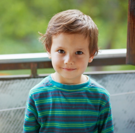 Portrait of a small boy standing and smiling to you.